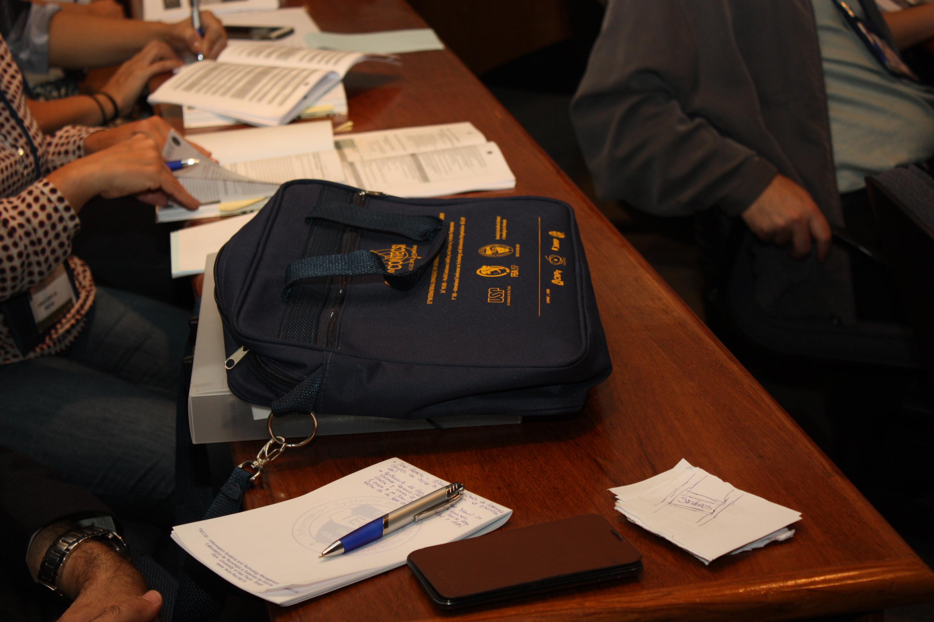 Detalhe dos materiais distribuídos no 12º CONTECSI - pasta, bloco de anotações e caneta