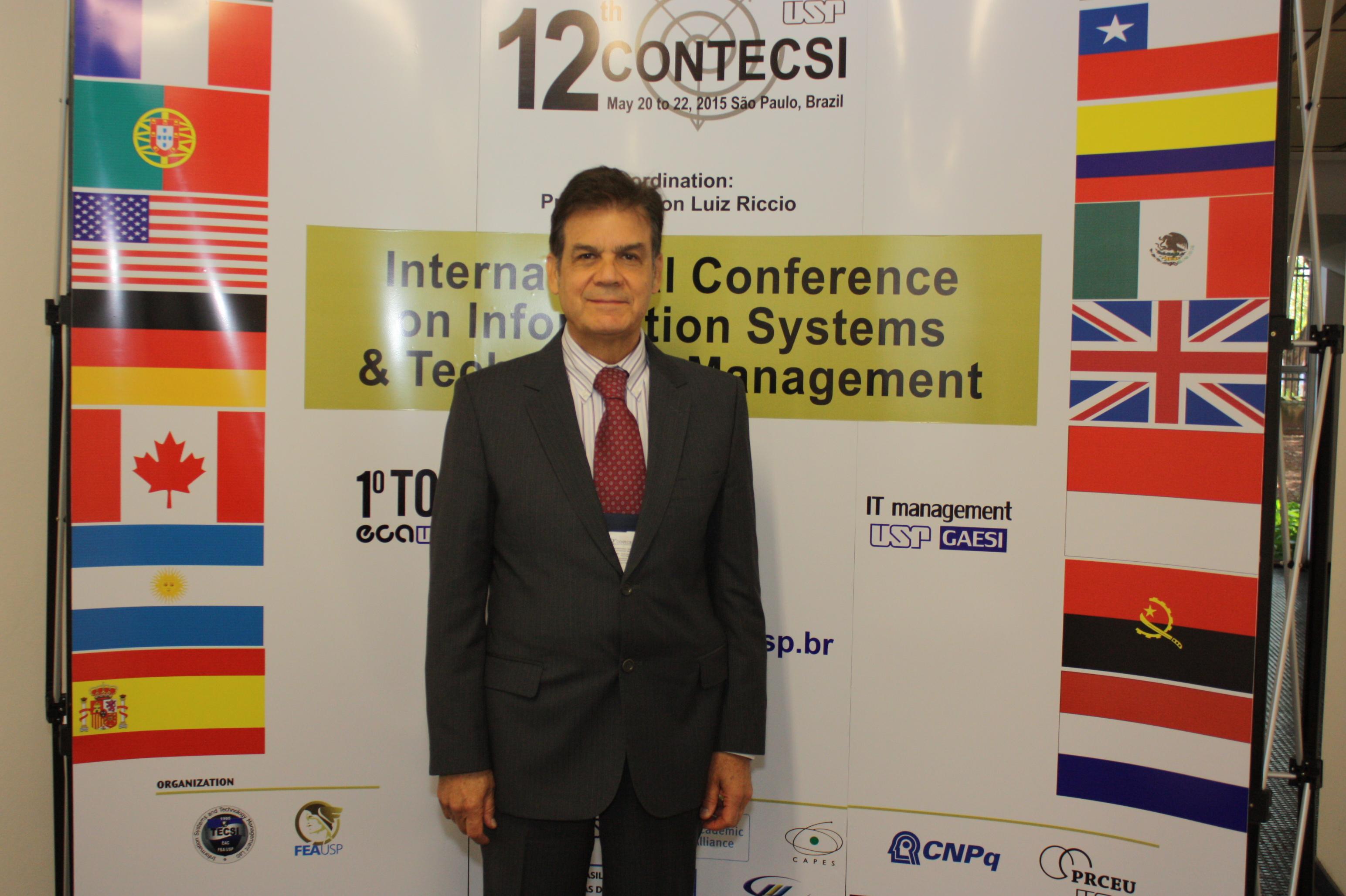Edson Luiz Riccio em frente ao banner do 12º CONTECSI
