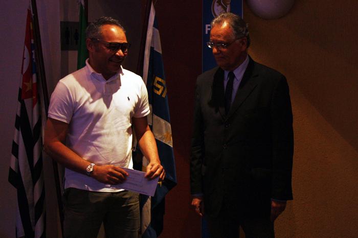 Prof. Wesley Mendes da Silva recebe o prêmio das mãos do Prof. Welington
