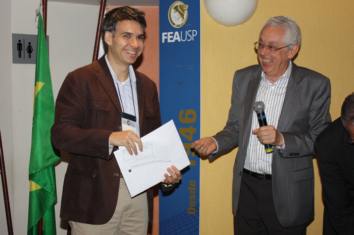 Prof. Lucas de Barros em nome do Prof. Luiz Paulo Fávero recebe o prêmio das mãos do Prof. Eliseu Martins