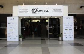 Fachada da entrada do Congresso, duas colunas e uma trave, brancas, com os logotipos do 12º CONTECSI e de seus apoiadores