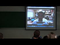 Foto do evento com a imagem do professor na tela de projeção
