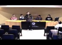 foto da mesa com o grupo de alunos e um aluno no meio da imagem de pé com o microfone