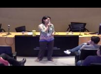 professora no centro da imagem com o microfone apresentado e uma mesa no fundo