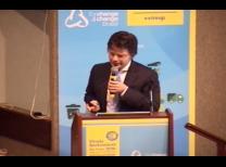 foto do evento com o o palestrante no meio da tela com o microfone