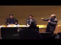foto do evento com dois professores sentados ao fundo o professor Guilhoto a direita com o microfone