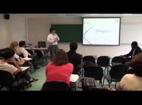 foto da sala de aula com o professor em pé a esquerda da tela