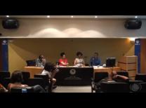 foto do evento com o painel de palestrantes no meio da imagem, com os quatro palestrantes sentados lado a lado