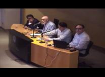 foto do evento com o painel de palestrantes no meio da imagem, com os quatro palestrantes sentados em linha